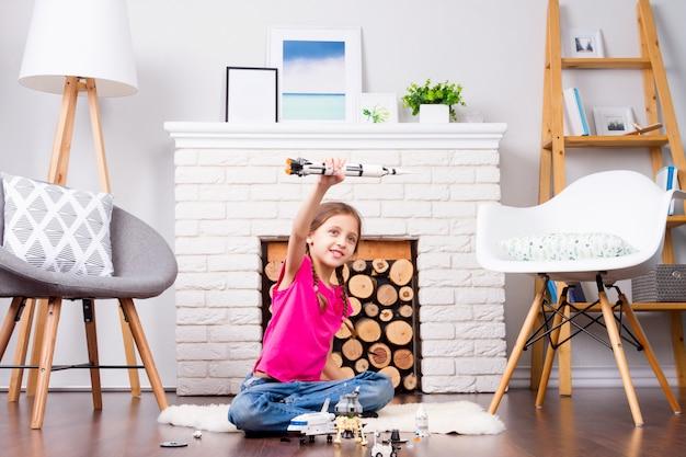 Fêmea de menina criança brincando com o construtor de brinquedos do cosmos: boneca de foguete, ônibus, rover, satélite e astronauta no interior confortável em casa no piso de madeira