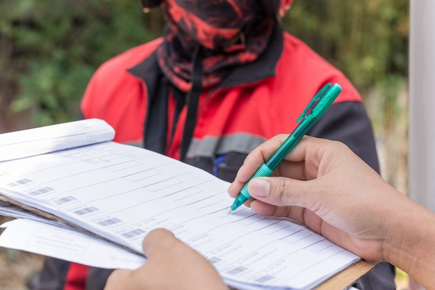 Fêmea de serviço de entrega mãos segurando a caneta, assinar o documento de entrega.