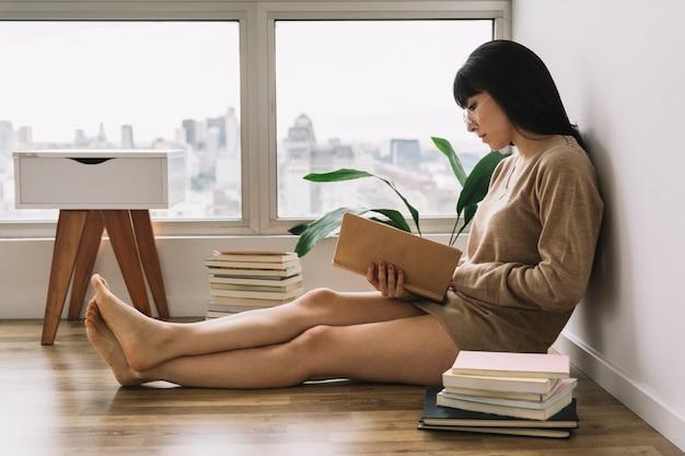 Fêmea descalça lendo no chão