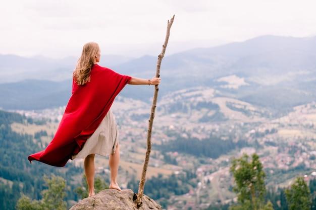 Fêmea desconhecida no vestido e capa vermelha em pé na pedra no topo da montanha. mulher loira com os pés descalços com vara de madeira grande, apreciando a paisagem da natureza do ponto de vista.
