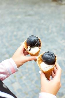 Fêmea em carvão de mão e sorvete de baunilha