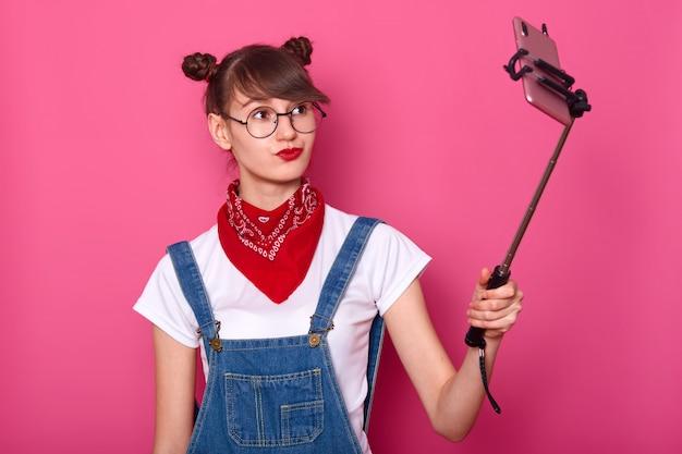 Fêmea em casual camiseta branca, macacão, bandana vermelha no pescoço e óculos redondos. adolescente adorável mantém os lábios arredondados
