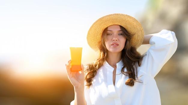 Fêmea em chapéu de palha praia segurando protetor solar