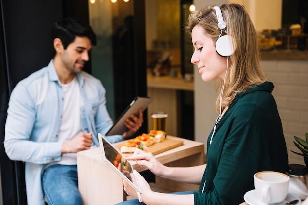 Fêmea em fones de ouvido usando tablet no café