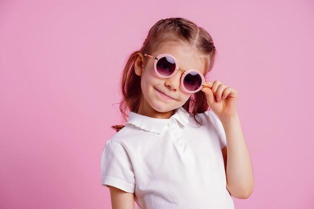 Fêmea em óculos de sol redondos rosa isolado na rosa