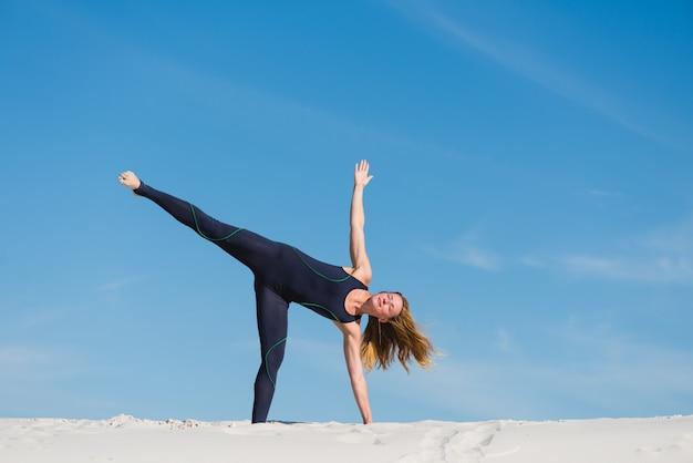 Fêmea em pose de triângulo de ioga no deserto ao ar livre