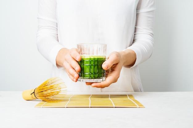 Fêmea em roupas brancas, segurando o copo com chá matcha japonês ou smoothie verde