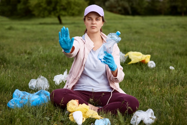 Fêmea em traje casual, sentado na grama verde, segurando a garrafa de plástico usada e mostrando o gesto de parada, luta voluntária com poluição, pede para manter o planeta longe do lixo.
