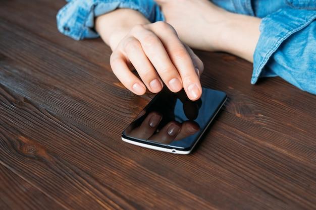 Fêmea em uma camisa jeans segurando o celular e sentado em uma mesa de madeira