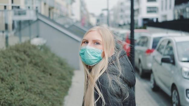 Fêmea em uma máscara médica escapando de alguém na rua.