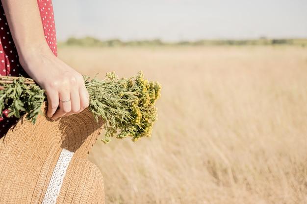 Fêmea em vestido de bolinhas com chapéu de fazendeiro e buquê de flores na mão, cores desbotadas com estilo retrô