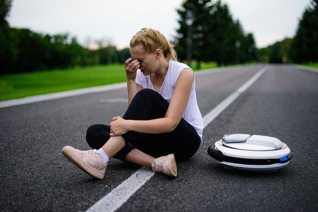 Fêmea esfrega a perna ferida. menina chateada sentar na estrada.