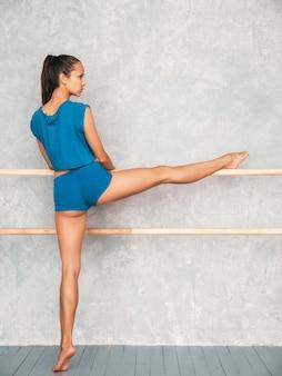 Fêmea, estendendo-se antes do treino, perto da parede cinza no estúdio