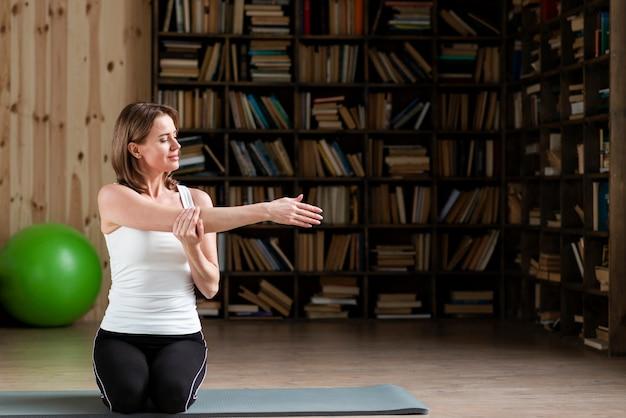 Fêmea, esticando os braços no tapete de ioga