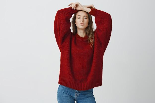 Fêmea europeia sensual e segura de si mesma na camisola solta vermelha, esticando o olhar sedutor e atrevido, apertando os olhos, levantando as mãos na cabeça, relaxando posando sonhadora e sexy contra