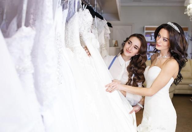 Fêmea experimentando o vestido de casamento em uma loja com assistente de mulheres.