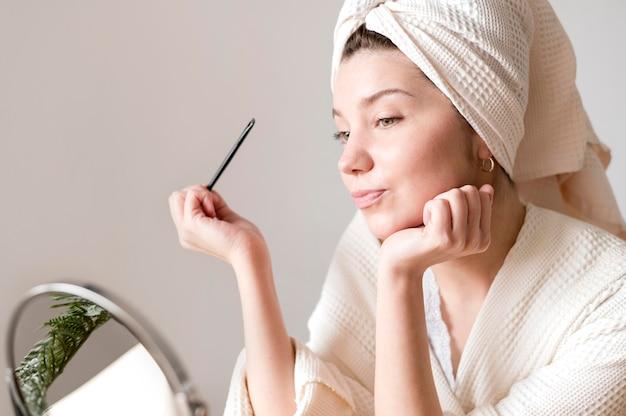 Fêmea fazendo as sobrancelhas em casa