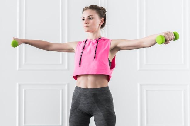 Fêmea fazendo exercícios com halteres