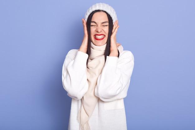 Fêmea feliz tocando a cabeça com as mãos, fechando os olhos, abrindo a boca amplamente, sendo surpreendida