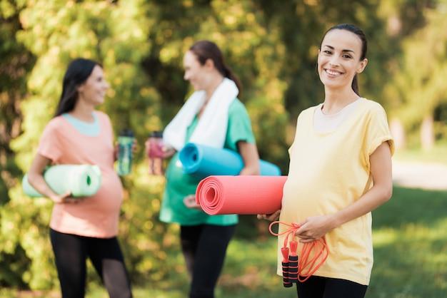 Fêmea grávida de sorriso no parque.