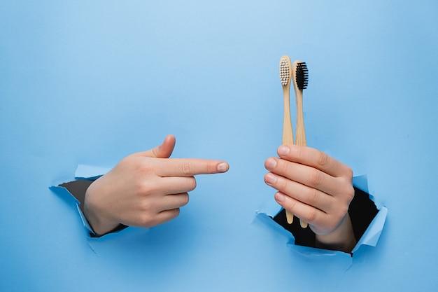 Fêmea irreconhecível apontando nas escovas de dentes de bambu eco através de uma parede de papel azul rasgado.