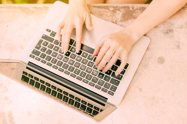 Fêmea irreconhecível digitando no teclado do laptop ao ar livre