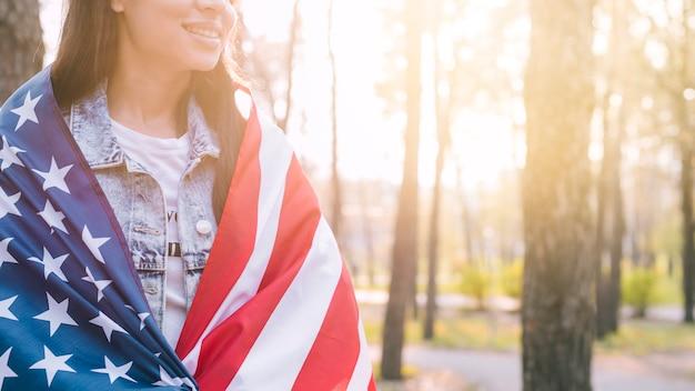 Fêmea irreconhecível envolvendo na bandeira americana no dia quente de verão