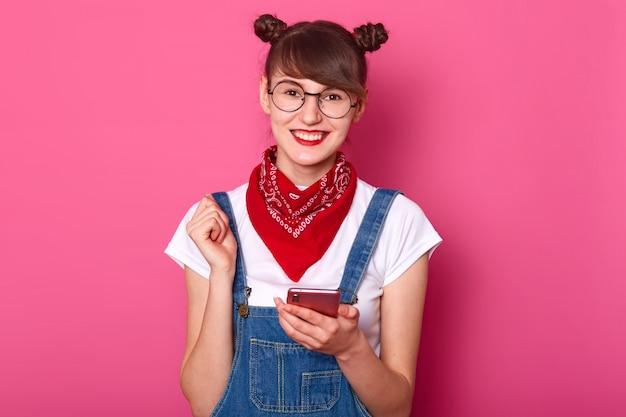 Fêmea jovem adolescente feliz com cachos, óculos, bandana na nack, vestido jeans macacão e camiseta branca, parece satisfeito enquanto segura o telefone móvel na mão isolado na rosa.