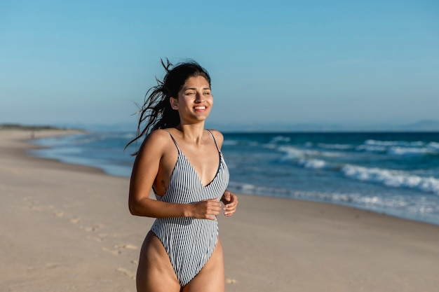 Fêmea jovem alegre, correndo ao longo do litoral