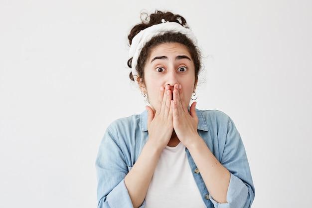Fêmea jovem assustada chocada, com cabelos escuros, vestindo camisa de brim e jeans, cobrindo a boca com as duas mãos, mantendo segredo. garota não quer espalhar informações confidenciais, posa com olhos arregalados