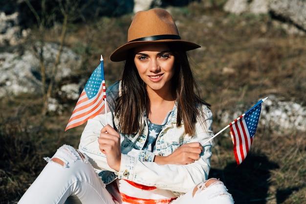 Fêmea jovem atraente sentado com bandeiras americanas na natureza