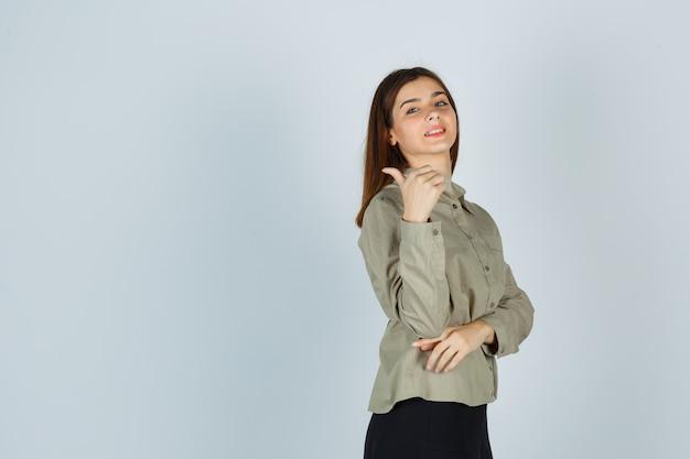 Fêmea jovem bonita aparecendo polegar na camisa, saia e olhando feliz. vista frontal.