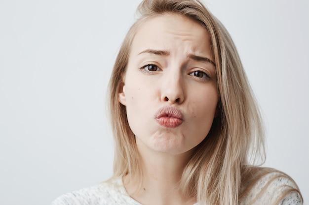 Fêmea jovem bonita com pele pálida, longos cabelos loiros, usa blusa casual, arredonda os lábios, parece coquete