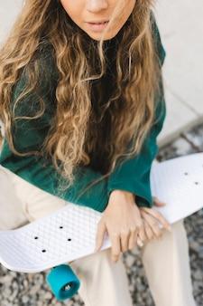 Fêmea jovem close-up ao ar livre com skate