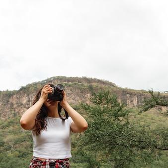 Fêmea jovem de baixo ângulo com câmera