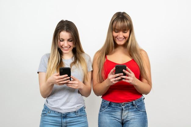 Fêmea jovem e sorridente usando celular
