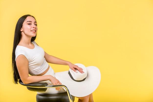 Fêmea jovem elegante sentado na cadeira