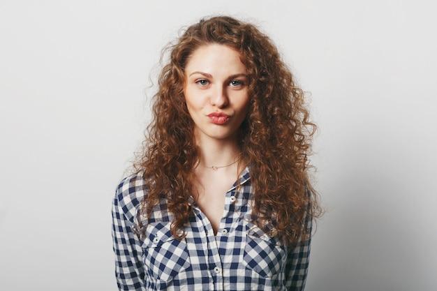 Fêmea jovem encantada com aparência atraente faz beicinho nos lábios e faz uma careta