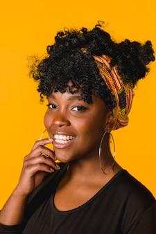 Fêmea jovem encaracolado afro-americana positiva em fundo colorido