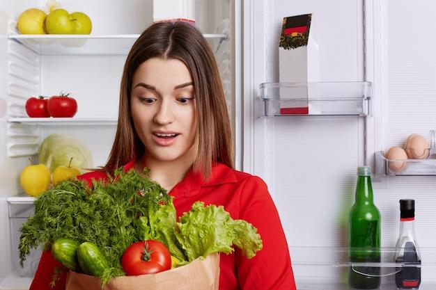 Fêmea jovem espantada com expressão de surpresa olha legumes, esquece de comprar algo na mercearia, fica na cozinha perto da geladeira.