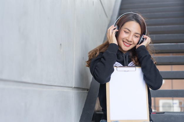 Fêmea jovem estudante sentar nas escadas com a pasta e cópia-livro e fone de ouvido na área do campus