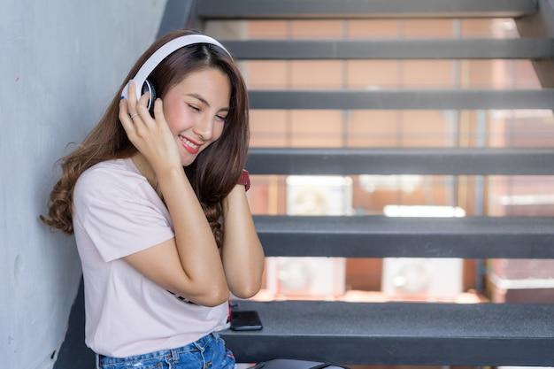Fêmea jovem estudante sentar nas escadas com fone de ouvido na área do campus