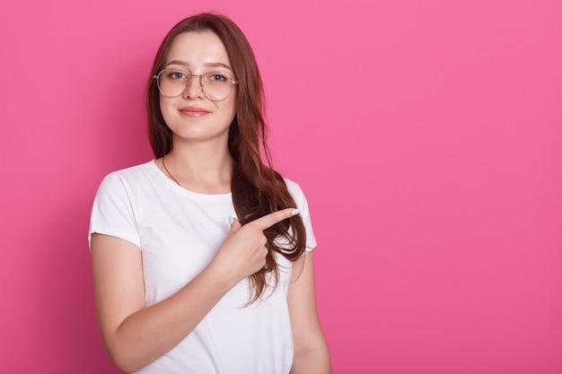 Fêmea jovem feliz sorrindo amplamente e olhando diretamente para a câmera, apontando de lado com o dedo dianteiro, mostrando algo interessante. copie o espaço para o seu texto ou publicidade.
