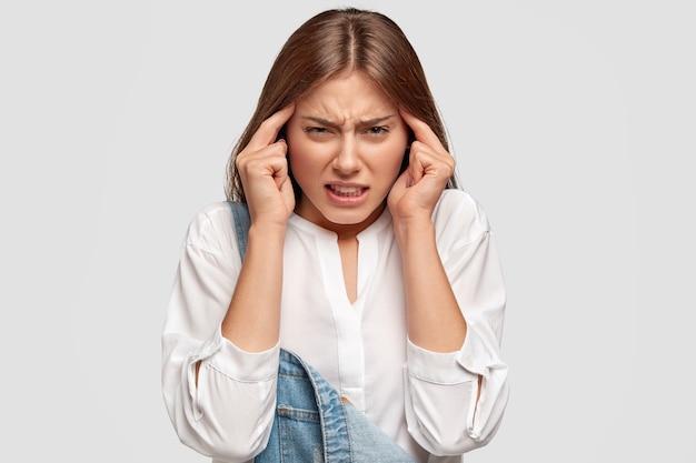 Fêmea jovem insatisfeita mantém as mãos nas têmporas, sofre de fortes dores de cabeça, parece estressante, vestida com roupa casual, posa contra uma parede branca. a mulher sente uma dor terrível.