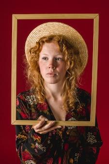 Fêmea jovem ruiva segurando o frame de madeira
