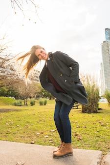 Fêmea jovem, sacudindo o cabelo no vento e sorrindo
