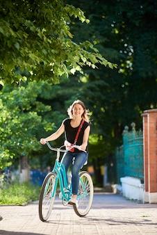 Fêmea jovem sorridente, andar de bicicleta azul no belo parque no dia de verão ensolarado