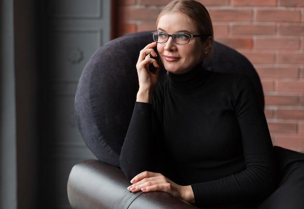 Fêmea jovem sorridente, falando no celular