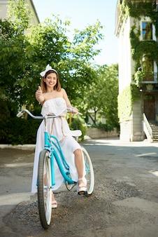 Fêmea jovem sorridente, mostrando os polegares enquanto andava de bicicleta turquesa por uma bela rua ensolarada