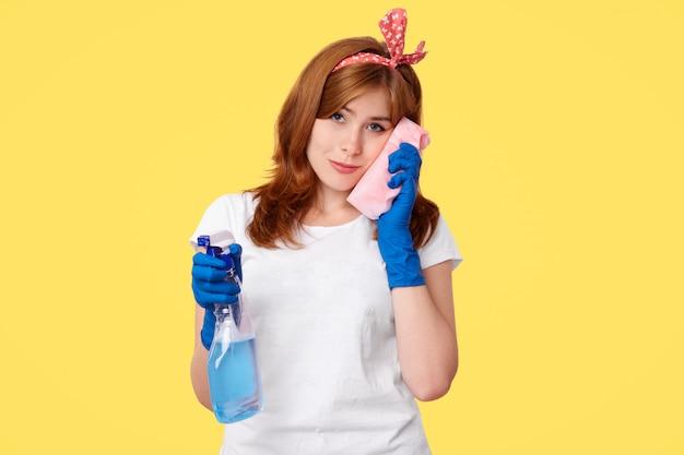 Fêmea jovem triste sobrecarregada limpa as janelas com spray e esponja de lavar roupa, sente-se sozinha e cansada, aperta-se contra a vontade, quer descansar bem, usa luvas de borracha, isoladas na parede amarela